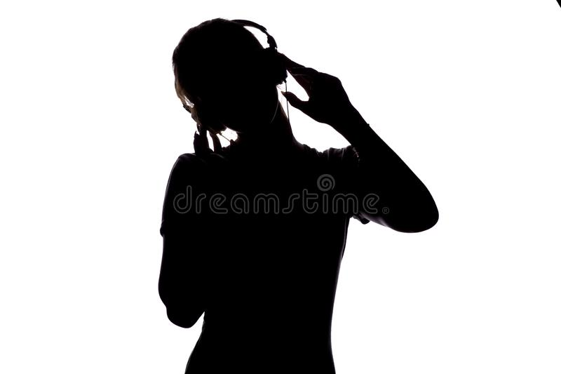 Silhouet van een gelukkig meisje het luisteren lied en het ontspannen in hoofdtelefoons, cijfer die van tennager zich aan de muzi stock fotografie