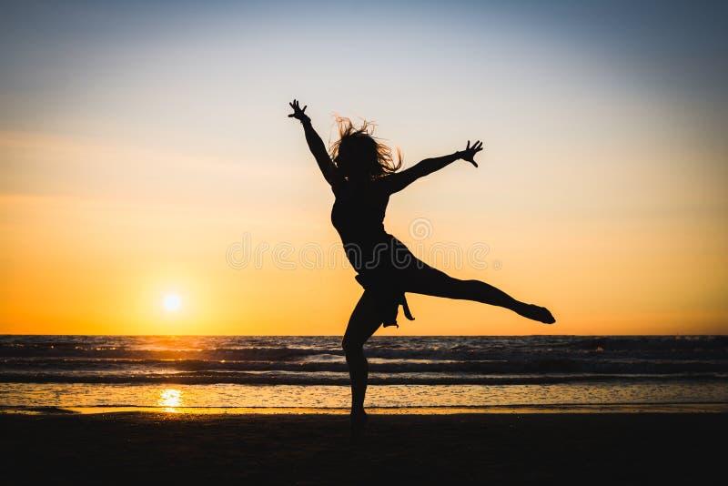 Silhouet van een gelukkig mooi dansersmeisje bij zonsondergang stock afbeeldingen
