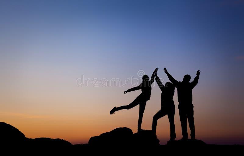 Silhouet van een gelukkige die familie met wapens omhoog tegen mooie hemel worden opgeheven De zonsondergang van de zomer royalty-vrije stock afbeelding