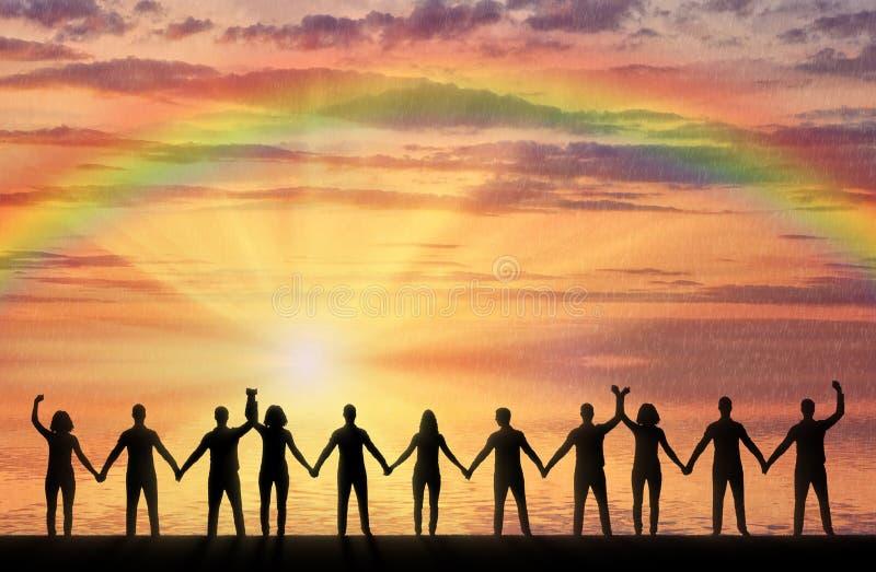 Silhouet van een groep gelukkige mensen die handen houden door het overzees bij zonsondergang met een regenboog stock fotografie