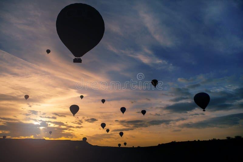 Silhouet van een groep hete luchtballons die over de heuvel vliegen stock foto