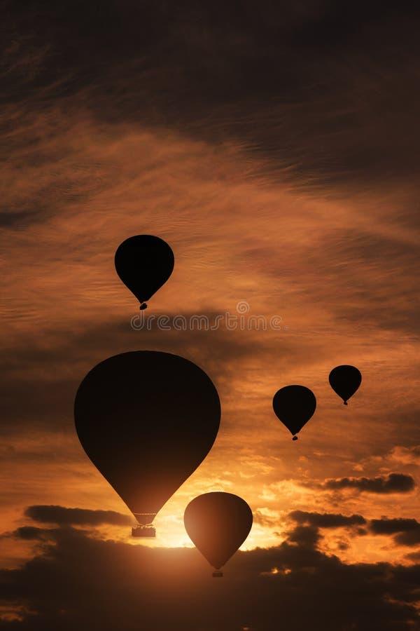 Silhouet van een groep hete luchtballons die over de heuvel vliegen stock foto's