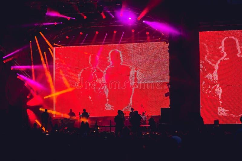 Silhouet van een grote menigte bij overleg tegen een helder aangestoken stadium Het overleg van de nachtrots met omhoog mensen di stock foto