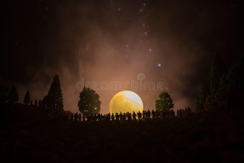 Silhouet van een grote menigte van mensen in bos bij nacht het letten op bij het toenemen grote volle maan Verfraaide achtergrond royalty-vrije stock afbeeldingen