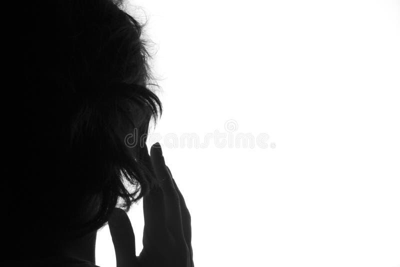 Silhouet van een handpersoon in terug met vinger dichtbij het oor op een witte achtergrond Hoor concept of luister royalty-vrije stock afbeeldingen