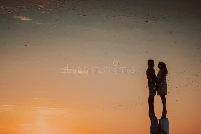 Silhouet van een houdend van paar bij zonsondergang dichtbij het overzees royalty-vrije stock foto