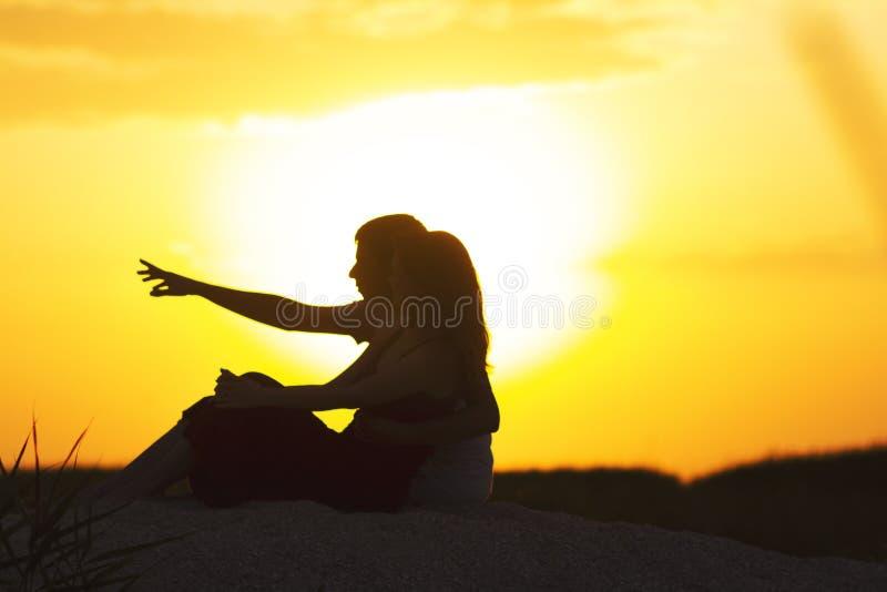 Silhouet van een houdend van paar bij zonsondergangzitting op zand op het strand, het cijfer van een man en een vrouw in liefde,  royalty-vrije stock foto's