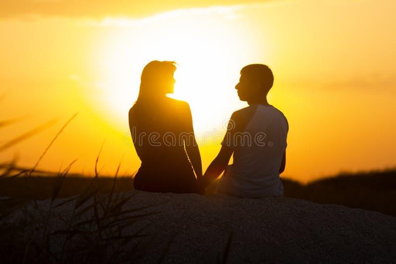 Silhouet van een houdend van paar bij zonsondergangzitting op zand op het strand, het cijfer van een man en een vrouw in liefde,  royalty-vrije stock afbeeldingen