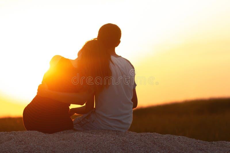 Silhouet van een houdend van paar bij zonsondergangzitting op zand op het strand, het cijfer van een man en een vrouw in liefde,  royalty-vrije stock fotografie