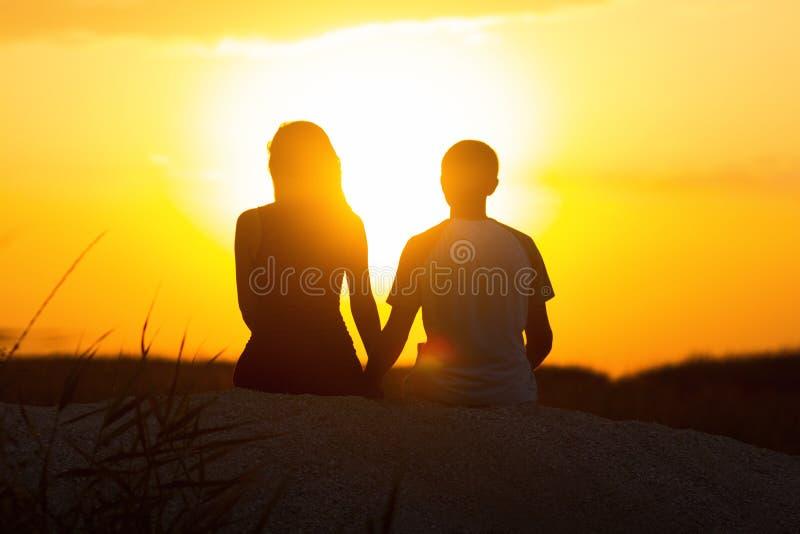 Silhouet van een houdend van paar bij zonsondergangzitting op zand op het strand, het cijfer van een man en een vrouw in liefde,  stock foto