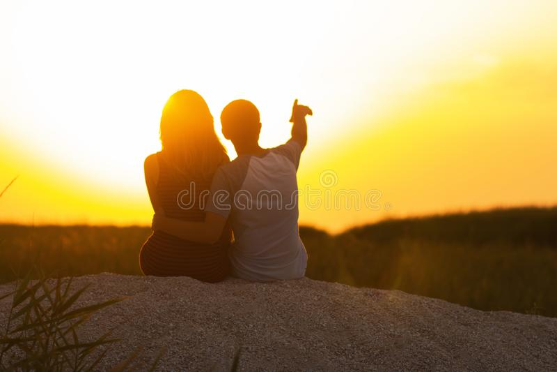 Silhouet van een houdend van paar bij zonsondergangzitting op zand op het strand, het cijfer van een man en een vrouw in liefde,  royalty-vrije stock foto