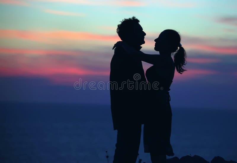 Silhouet van een houdend van paar tegen de hemel na zonsondergang royalty-vrije stock fotografie