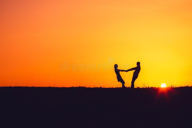 Silhouet van een houdend van paar bij zonsondergang stock afbeelding