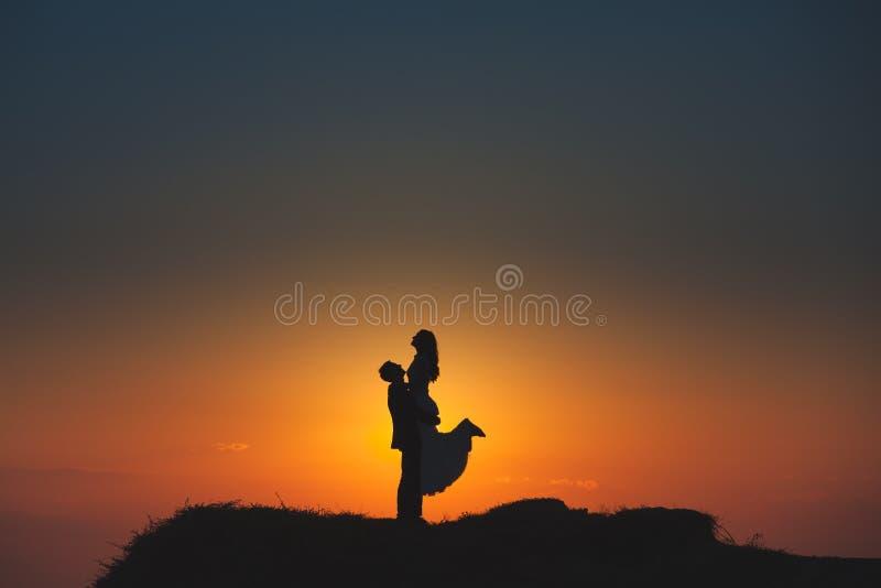 Silhouet van een houdend van paar op de achtergrond van de het plaatsen zon royalty-vrije stock afbeelding