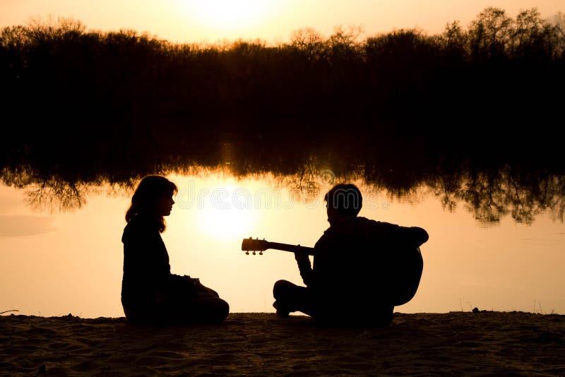 Silhouet van een jong jongen en een meisje op het strand met een gitaar stock foto