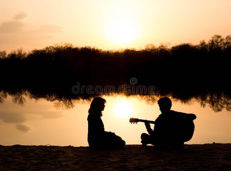 Silhouet van een jong jongen en een meisje op het strand met een gitaar stock afbeelding