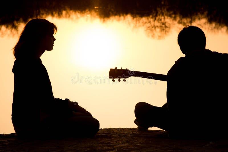 Silhouet van een jong jongen en een meisje op het strand met een gitaar stock fotografie