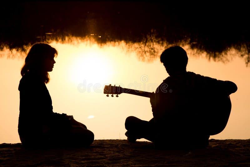 Silhouet van een jong jongen en een meisje op het strand met een gitaar stock foto's