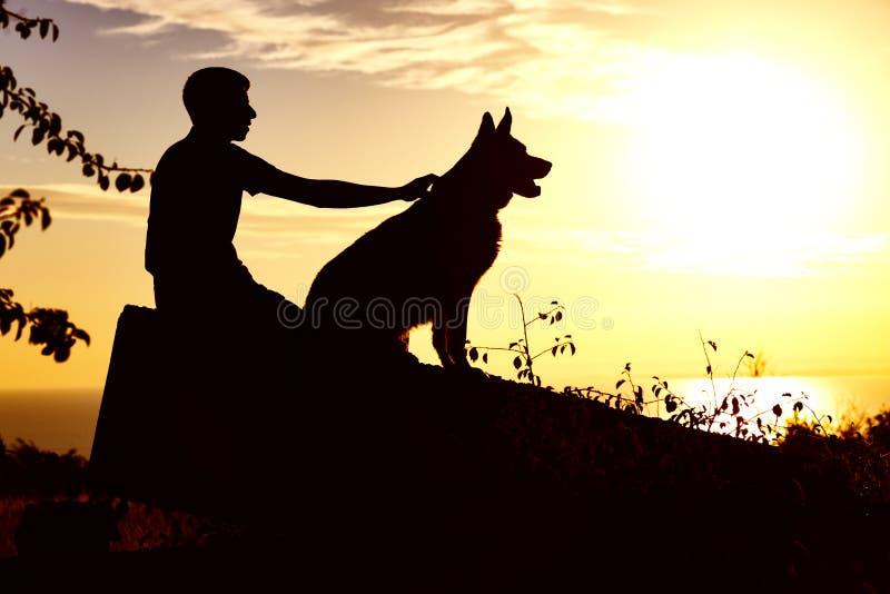 Silhouet van een jong mannetje die met een hond op het gebied bij zonsondergang lopen, kerel met een Duitse herder die de zomer v royalty-vrije stock afbeelding
