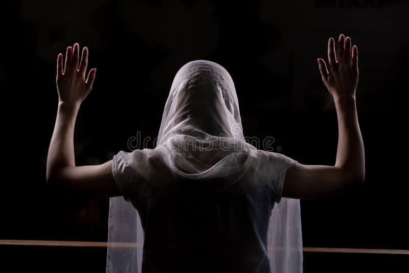 Silhouet van een jong meisje dat in kerk en het bidden met omhoog opgeheven handen zit Close-upmening van erachter Backlight stock afbeelding