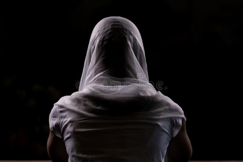 Silhouet van een jong meisje dat in kerk en het bidden zit Close-upmening van erachter Backlight stock foto