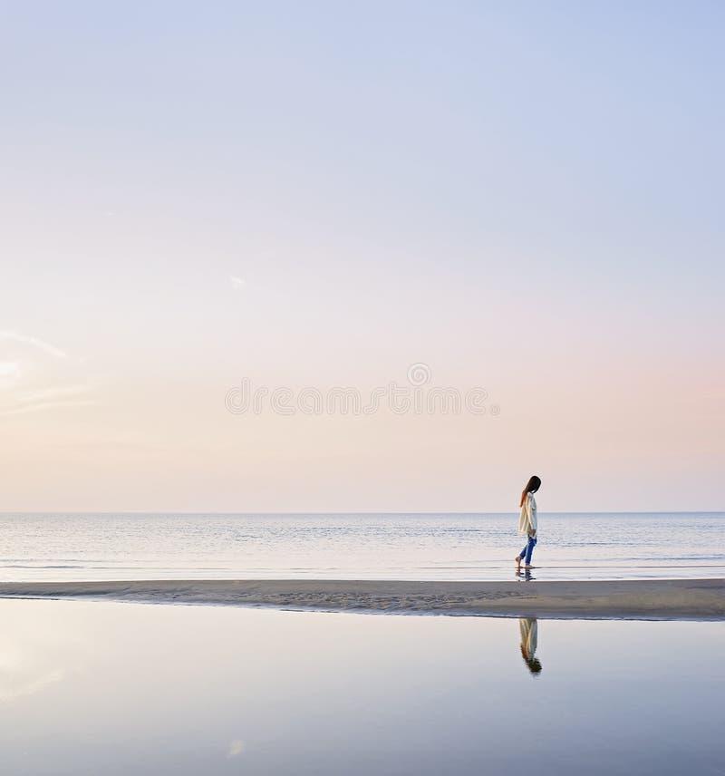 Silhouet van een jong meisje die bij het overzees lopen royalty-vrije stock fotografie