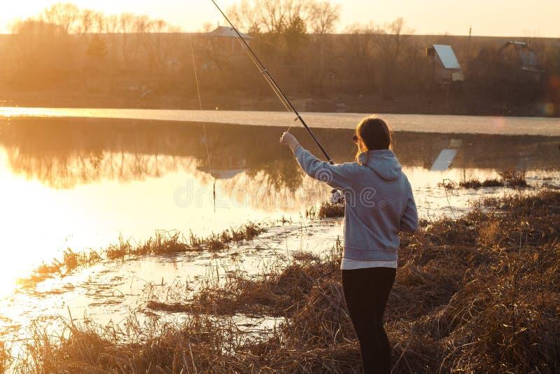 Silhouet van een jong meisje die bij zonsondergang dichtbij het meer vissen royalty-vrije stock foto's