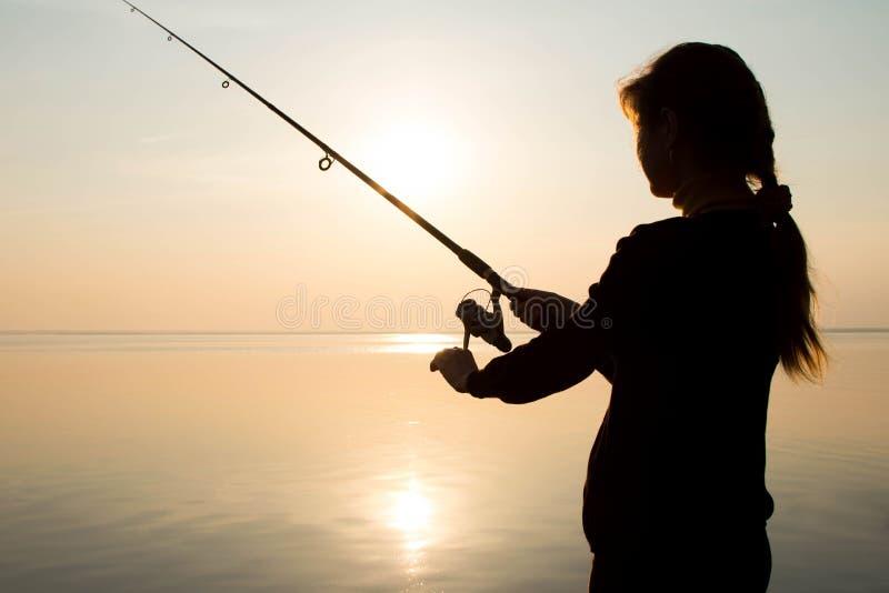 Silhouet van een jong meisje die bij zonsondergang dichtbij het overzees vissen royalty-vrije stock foto's