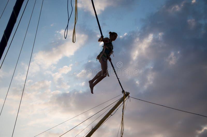 Silhouet van een jong meisje die op een bungee op een trampoline op een zonsondergangachtergrond springen op een overzees royalty-vrije stock fotografie