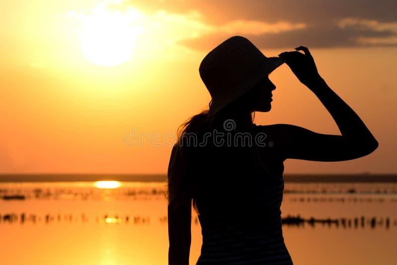 Silhouet van een jong meisje op de achtergrond van het overzees stock afbeeldingen