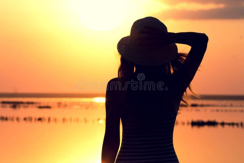 Silhouet van een jong meisje op het overzees in een hoed royalty-vrije stock afbeelding