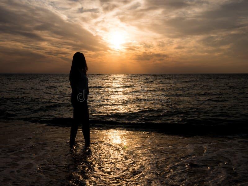 Silhouet van een jong meisje op het strand het jonge meisje loopt bij zonsondergang door het overzees stock afbeeldingen