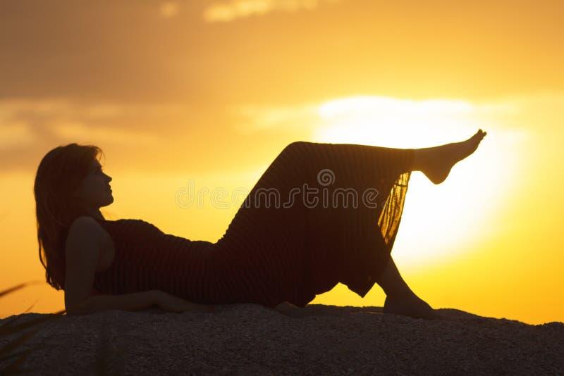 Silhouet van een jong mooi meisje die in een kleding op het zand liggen en van de zonsondergang, het cijfer genieten van een vrou stock foto