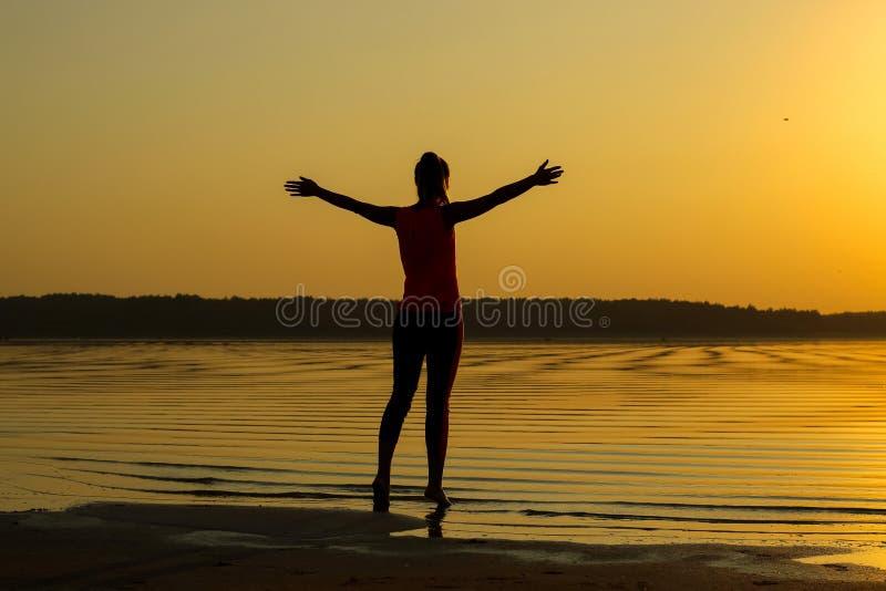 Silhouet van een jong mooi meisje met handen omhoog tegen de achtergrond van de zonsondergang in de bezinning van de overzeese ku stock fotografie