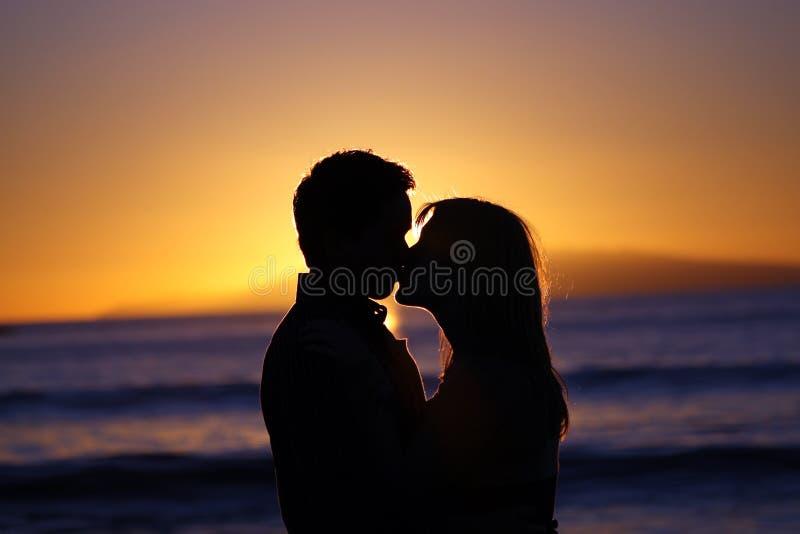 Silhouet van een jong paar dat bij het strand kust royalty-vrije stock afbeelding