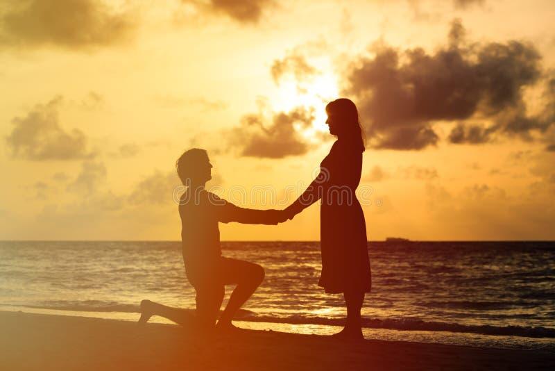 Silhouet van een jong romantisch paar bij zonsondergangstrand stock afbeelding