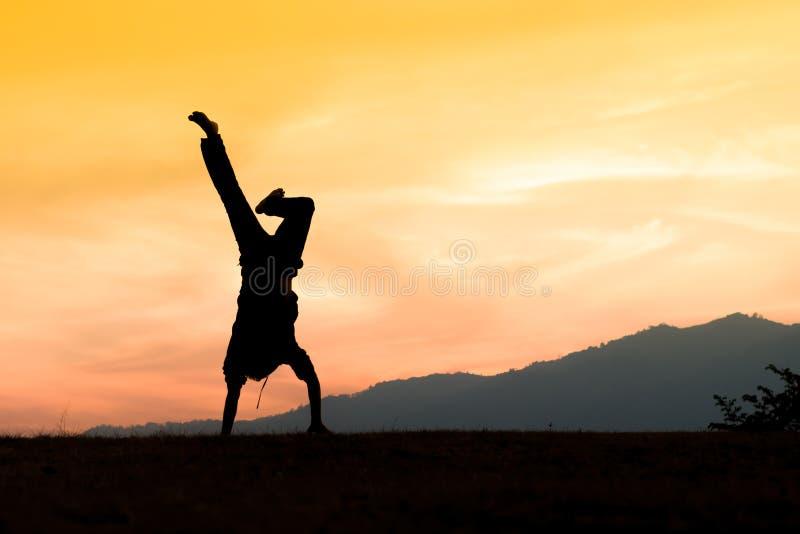 Silhouet van een jonge acrobatische mens die zich op handen bevinden stock foto