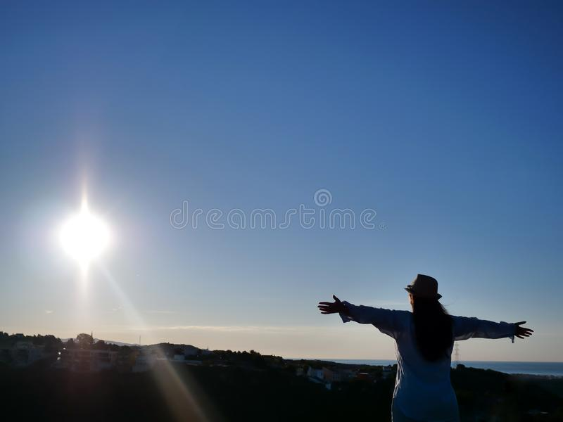Silhouet van een jonge donkerbruine vrouw met opgeheven wapens op de achtergrond van de zonsopgang, de stralen van de zon, copysp stock foto