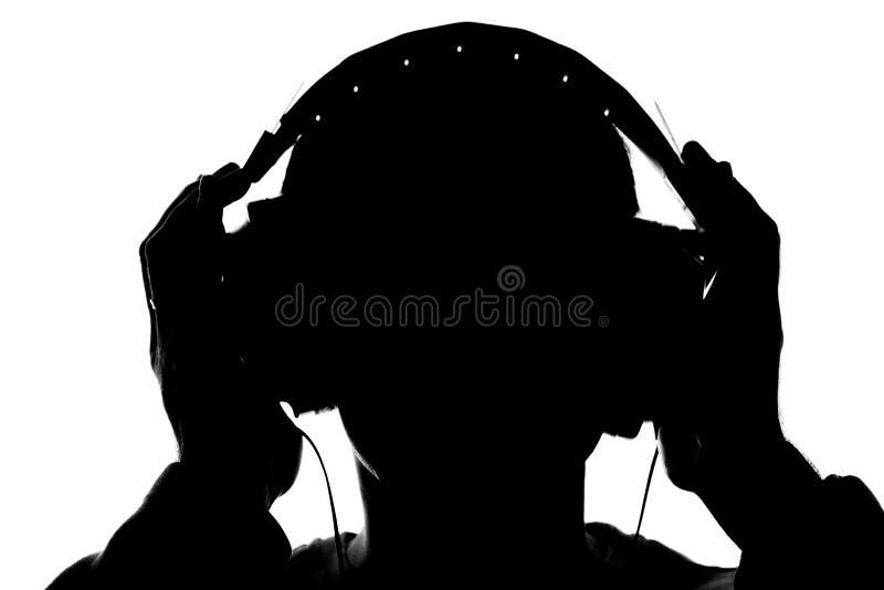 Silhouet van een jonge mens die aan muziek met hoofdtelefoons luisteren stock fotografie