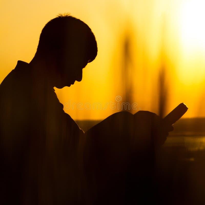 Silhouet van een jonge mens met een Bijbel, mannetje aan God in aard bidden, het concept godsdienst en spiritualiteit die stock foto's