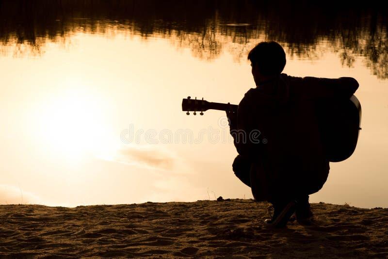 silhouet van een jonge mens met een gitaar stock foto's