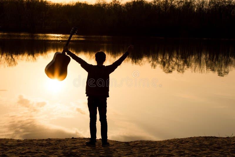 silhouet van een jonge mens met een gitaar stock afbeelding