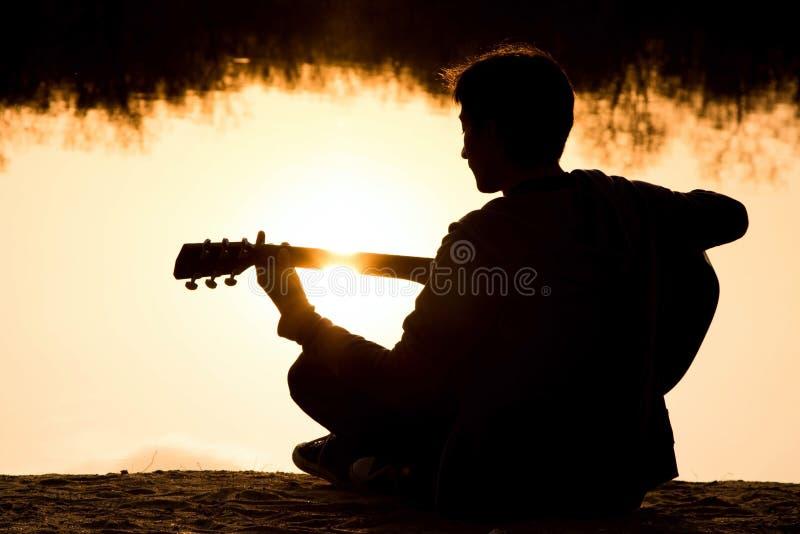 silhouet van een jonge mens met een gitaar royalty-vrije stock foto's