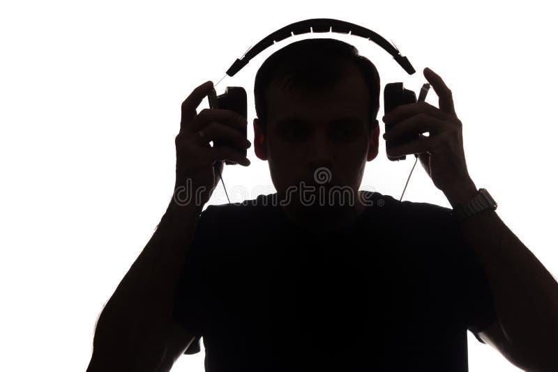 Silhouet van een jonge mens met een smartphone met hoofdtelefoons royalty-vrije stock foto's