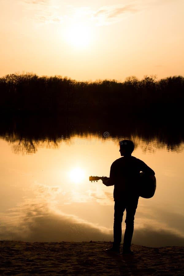 Silhouet van een jonge mens op het strand met een gitaar stock foto's