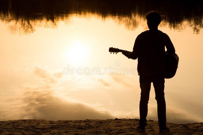 Silhouet van een jonge mens op het strand met een gitaar royalty-vrije stock afbeelding