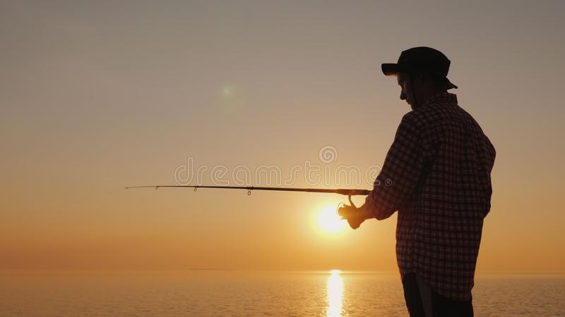 Silhouet van een jonge visser die op het strand bij zonsondergang vissen Zachte nadruk stock foto