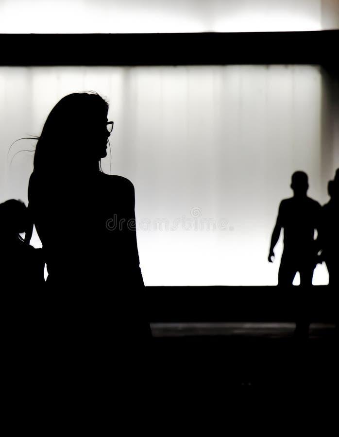 Silhouet van een jonge vrouw die alleen in de nacht lopen royalty-vrije stock foto's