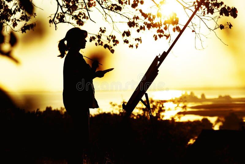 Silhouet van een jonge vrouw die een beeld op een schildersezel op aard, wijfje trekken zich onder boom met borstel bevinden en h stock afbeelding