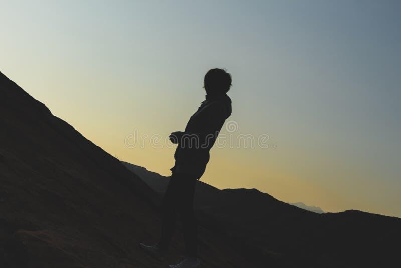 Silhouet van een jonge vrouw die op de heuvel wandelen stock foto